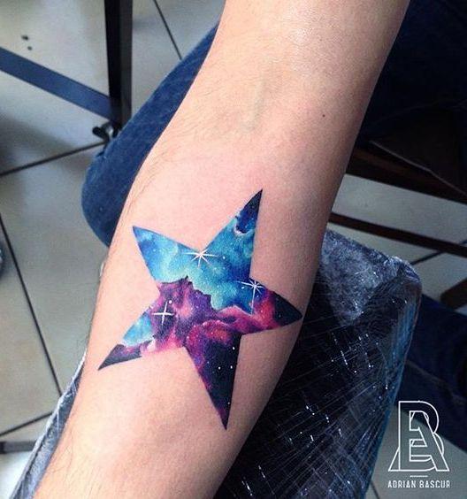 Tatouage femme grande etoile remplie avec viel etoilee bleu et violet avant bras